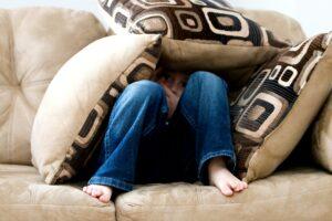 Child hiding underneath cushions